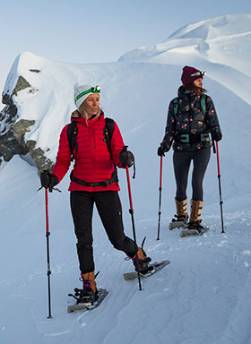 women snowshoeing on a mountain